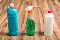 Flaschen und Sprayprodukte für Haushaltsreinigung auf dem Bretterboden Abwaschflüssigkeit und -schwämme Stockfoto