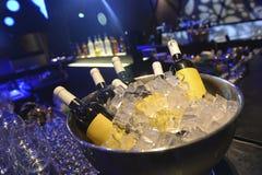 Flaschen Weißwein auf Eis und nahe gelegenen leeren Gläsern für Wein stockfotografie