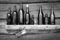 Flaschen, Weinglas und Glas stehen auf einem Regal lizenzfreies stockbild