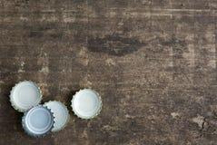 Flaschenkapseln auf rustikalem hölzernem Hintergrund Lizenzfreie Stockfotografie