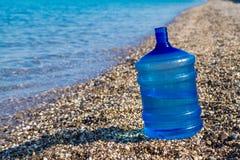 Flaschenständer eines große Wassers auf dem Strand, stockbilder