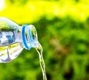 Flaschenwasser machte zum Plastik auf dem Holz und Baum undeutlichen bokeh Hintergrund im Garten Unter Verwendung der Tapete für  Lizenzfreies Stockfoto