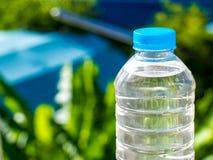 Flaschenwasser machte zum Plastik auf dem Holz und Baum undeutlichen bokeh Hintergrund im Garten Unter Verwendung der Tapete für  Lizenzfreies Stockbild