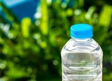 Flaschenwasser machte zum Plastik auf dem Holz und Baum undeutlichen bokeh Hintergrund im Garten Unter Verwendung der Tapete für  Stockfotografie