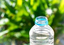 Flaschenwasser machte zum Plastik auf dem Holz und Baum undeutlichen bokeh Hintergrund im Garten Unter Verwendung der Tapete für  Stockfoto