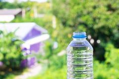 Flaschenwasser machte zum Plastik auf dem Holz und Baum undeutlichen bokeh Hintergrund im Garten Unter Verwendung der Tapete für  Stockbild