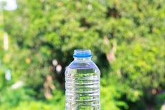 Flaschenwasser machte zum Plastik auf dem Holz und Baum undeutlichen bokeh Hintergrund im Garten Unter Verwendung der Tapete für  Lizenzfreie Stockbilder