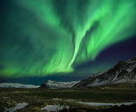 Flash of Aurora polaris. Above mountains Stock Image