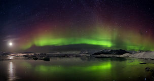 Flash of Aurora polaris. Above water Royalty Free Stock Photos