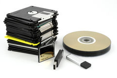 Flash, card and floppy disks. Flash memory devices, cd`s and pile of floppy disks on white background royalty free stock photography