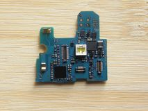 Flash component of smartphone. On circuit board kept on wooden table royalty free stock image