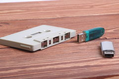 Flash disk and audio cassette on wooden background Stock Photography
