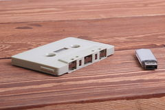 Flash disk and audio cassette on wooden background Stock Image