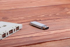 Flash disk and audio cassette on wooden background Royalty Free Stock Image