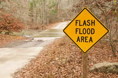 Flash Flood Area Sign. With stream crossing behind it stock photos