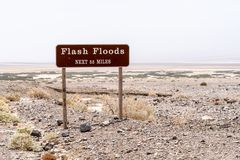 Flash Floods warning sign warns motorists of potential dangerous flooding on roads during rain and monsoon season in California`s. Death Valley National Park stock photos