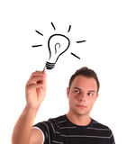 Flash of genius. A handsome young man sketching a stylized light bulb. All on white background Stock Image