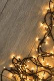 Flash lights. Yellow christmas flash lights garland on wooden floor Royalty Free Stock Image