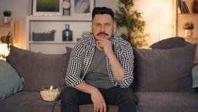Flash noticioso de observação do indivíduo emocional na tevê com a cara triste que senta-se no sofá em casa vídeos de arquivo