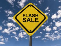 Flash sale. Text 'flash sale' in black uppercase letters on a yellow highway style sign board, blue sky and cloud background Stock Image