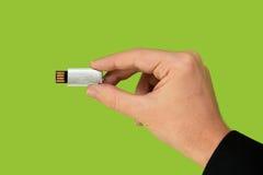 Flash-Speicher an Hand mit lokalisiertem grünem Hintergrund Stockfotos