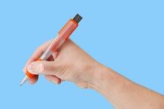 Flash-Speicher-Stock an Hand mit lokalisiertem orange Hintergrund Stockbild