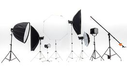 Flash studios of various sizes and accessories are placed together on white background. royalty free stock image