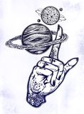 Inked hand, finger spinning Saturn space planet. Flash tattoo style astronomy. Inked human hand, finger spinning Saturn space planet. Dotwork ink tattoo vintage Stock Images