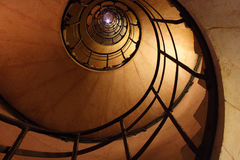 A flash at the top of the spiral stair. Looking up a spiral staircase with a photographer shooting downward Royalty Free Stock Photo