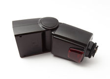 Flashgun over white background. A flashgun for DSLR camera over white background Royalty Free Stock Photo