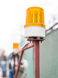Flashing Beacon. Orange flashing beacon in the place of work Royalty Free Stock Photos
