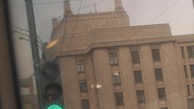 Flashing green traffic light in front of Moscow State University building. On winter cold gloomy clody day, slow motion stock footage