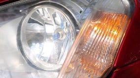 Car headlamp turn. Flashing headlights turn on a red modern car stock footage