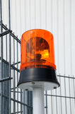 Flashing light. Photo of a round flashing light in front of an iron fence Stock Photo