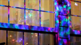 Flashing light display on a window with a Christmas tree stock footage