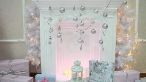 Flashing lights Christmas garland decorated with beautiful fireplace. New Year. White beautiful fireplace decorated with silver Christmas balls and pine cones stock video