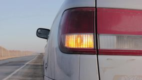 Flashing orange blinker light on rear lamp. car on a sidelines stock footage