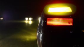 Flashing orange blinker light on sport car parked on side at night. Car light blinking. Traffic passing at background stock footage