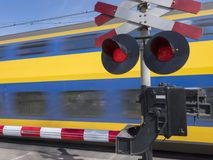 Flashing red lights while train passes railway crossing. Flashing red lights while blue and yellow train passes railway crossing Stock Images