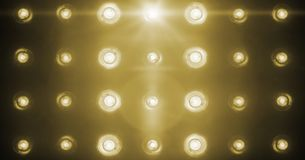 Flashing shiny golden stage lights entertainment, spotlight projectors in the dark, gold warm soft light spotlight strike on black. Background royalty free stock photo