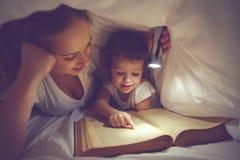 家庭读书上床时间 妈妈和儿童与flashl的阅读书 免版税图库摄影