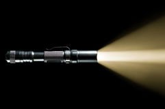 Flashlight with beam of light. Tactical police and military flashlight on black background with visible beam of light Stock Images