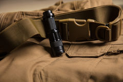 Flashlight and clasp on brown textile. Flashlight and clasp on brown textile Royalty Free Stock Photography