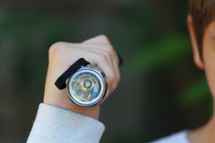 Flashlight. A close up view of someone holding up a flashlight towards the camera Royalty Free Stock Photo