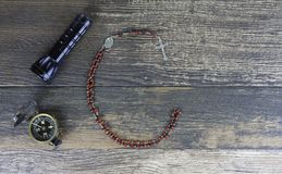 Flashlight, Compass and Rosary on Dark Brown Wood Stock Photos