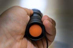 Flashlight on. Hand holding flashlight illuminating straight ahead Royalty Free Stock Photos