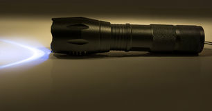 Flashlight on. Turned on flashlight standing on a flat surface Royalty Free Stock Images