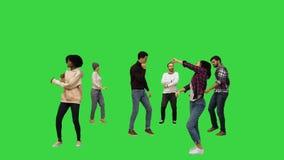 Flashmob: young people walk in and start dancing on a Green Screen, Chroma Key.