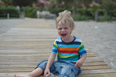 Flashy boy sits on a wooden walkway on the beach Stock Image