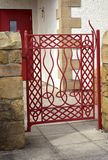 Flashy curb appeal. This red, flame gate has a combination of Celtic and modern design elements. It presents a unique entry portal and added curb appeal to this Stock Images